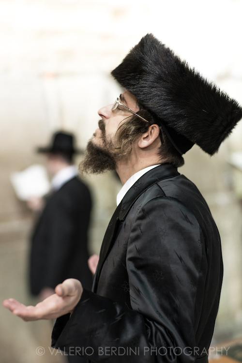 上图:一位哈雷迪犹太人穿着安息日的Bekishe黑丝长外套,在哭墙祷告。作为已婚男人,他在小圆帽Kippah之上又戴了Shtreimel大毛帽,表示对神特别尊重。