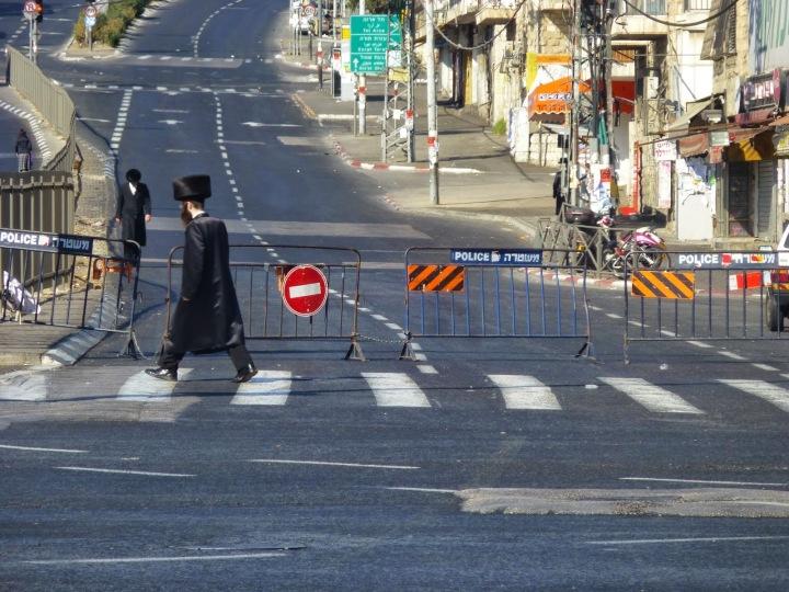 上图:2014年8月23日安息日的耶路撒冷街头,哈雷迪犹太人社区用路障挡住了街道,不准汽车经过。一位哈雷迪犹太人穿着安息日的Bekishe黑丝长外套步行到附近的会堂。