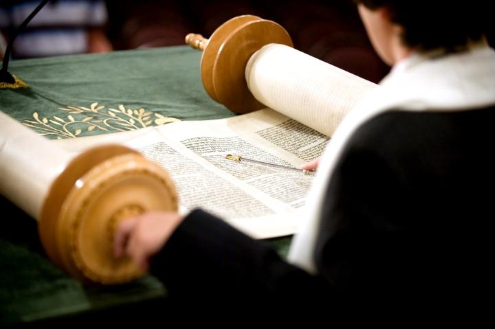 上图:一个犹太人在读摩西五经(妥拉)。犹太会堂里的希伯来圣经写在一卷卷的羊皮纸上,平时由会堂的执事放在经筒中保管,读时要展开,读完后再卷回原状。