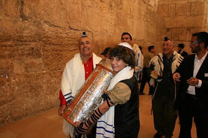 上图:一个13岁的犹太男孩在成为「诫命之子」的仪式上抱着一个经筒,里面是一卷希伯来圣经。