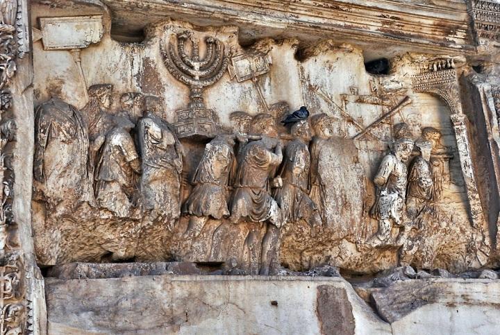 上图:提多凯旋门的浮雕,描绘罗马士兵扛着从耶路撒冷圣殿掳来的金灯台、长号和陈设饼桌。多米田皇帝在他哥哥提多皇帝去世后不久,建了一座大理石单拱凯旋门,以纪念提多率军于主70年摧毁耶路撒冷,平息了主后66年开始的犹太人起义。直到今天,许多犹太人拒绝从拱门下经过。1948年以色列复国时,大批人群从罗马犹太社区沿着与古罗马凯旋式相反的方向通过提图斯凯旋门。