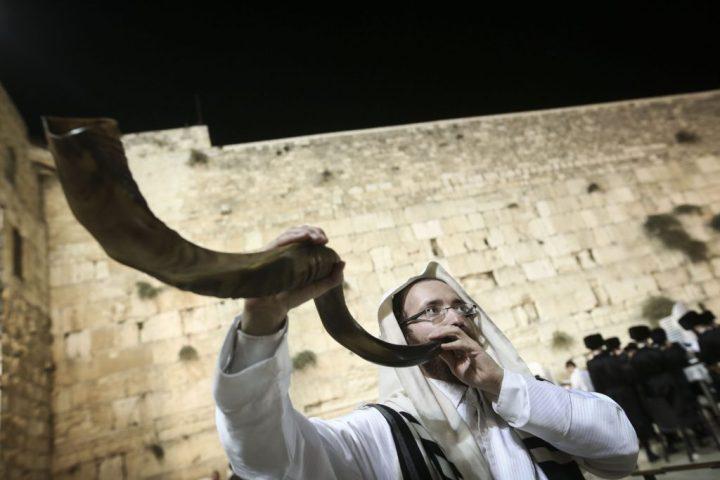 上图:一个犹太人于赎罪日在哭墙吹响羊角号(Shofar)。