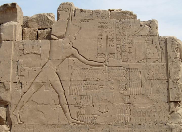 上图:埃及底比斯卡纳克神庙(Karnak Temple)的米吉多战役浮雕,描绘图特摩斯三世(Thutmose III,主前1479-1425年在位)正在用他「大能的手」在杀戮迦南人。浮雕上的米吉多战役铭文(Battle of Megiddo Inscription)用「他的手是如此大能」、「他的手比任何王都大能」来颂赞图特摩斯三世。米吉多战役(Battle of Megiddo,主前1457年)发生于出埃及之前约10年,是图特摩斯三世最著名的战功之一,使埃及重新控制了迦南北部,并且以此为基地进攻美索不达米亚。