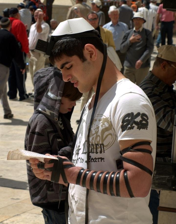 上图:一个犹太年轻人在前额和左臂上佩带经文匣(Tefillin),在耶路撒冷哭墙祷告。
