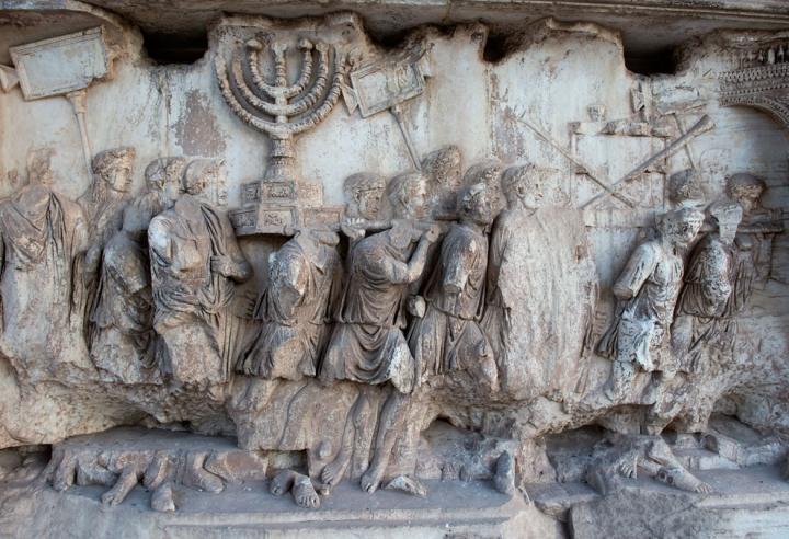 上图:提多凯旋门(Arch of Titus)上的浮雕,上面清楚描绘了第二圣殿时的金灯台和陈设饼桌子,桌上放着几个金杯,桌旁又靠着几支祭司的号筒。提多凯旋门是古罗马城遗址的一座大理石单拱凯旋门,用来纪念提多皇帝在主后70年征服和摧毁耶路撒冷。由于提多凯旋门上描绘了破坏耶路撒冷和亵渎圣殿,许多犹太人拒绝从拱门下经过,只有在1948年以色列复国时,大批人群从罗马犹太社区沿着与古罗马凯旋式相反的方向通过提多凯旋门。提多凯旋门拥有现存唯一的对第二圣殿器物的描绘。