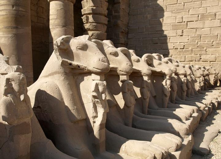 上图:建于主前2000年的古埃及卡纳克神庙(Temple of Karnak)入口的狮身公山羊像,公山羊象征古埃及最高神阿蒙-拉(Amun-Ra),站在公山羊脚前的是法老,象征最高神保护法老。多毛的公山羊是古实(Kush)的主神,埃及征服古实之后,认为古实主神就是太阳神阿蒙-拉,从此公山羊成为阿蒙-拉的化身之一。由于公山羊是多产的象征,所以公山羊形状的阿蒙神又与男性生殖神敏(Min)组合成阿蒙-敏(Amun-Min),进而演化成希腊淫乱的山羊神潘(Pan)。库努牡神(Khnum)也长着一个公羊头。