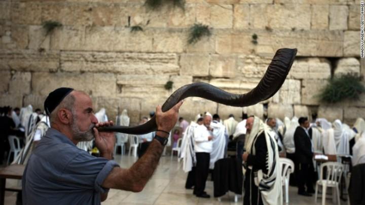 上图:一个犹太人于犹太新年在西墙吹响公羊角制成的羊角号(shofar)。犹太人被掳巴比伦回归以后,吹角节成为犹太人的农历新年(Rosh Hashanah),这一天要一百次吹响羊角号。