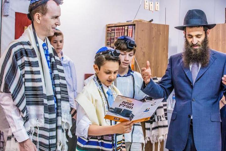 上图:一个犹太男孩在成为「诫命之子 Bar Mitzvah」的成人礼上诵读经文,他的前额上带着经文匣(Tefillin),身上披着祷告巾( Tallit)。犹太教男孩到了13岁,在律法上就和成年人有同样的权利和义务,被称为「诫命之子」。「诫命之子」每天都必须佩戴经文匣,并被安排在会堂中诵读妥拉、先知书和唱颂圣歌,带领聚会和公祷。犹太男孩在成人礼之前,由父母在神面前为自己的行为负责,而在成人礼之后,必须自己向神负责。因此,只有「诫命之子」,才可以「向耶和华许愿或起誓,要约束自己」(民三十2)。