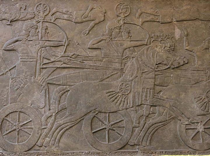 上图:主前九世纪亚述浮雕中的战车。亚兰的战车与此类似,这些战车以双马负轭拖拉,载人的小平台安装在后轴之上,车轮木制有辐。乘车者一人负责驾驶,一人则配有弓箭枪矛。二人站于车上,护栏只高及大腿中部。