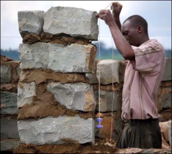 上图:一位非洲人吊起准绳筑墙。